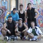 Gruppenbild der Drag Streets Boyz - 6 Personen vor Graffiti-Wand